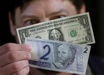 Nota de um dólar é fotografada ao lado de nota de dois reais quando esta foi lançada, no Banco Central, em Brasília. O dólar ganhava ainda mais força no final desta manhã, mesmo após a atuação do Banco Central, e subia 2 por cento ante o real, chegando ao patamar de 2,27 reais diante do nervosismo global com os sinais de que o programa de estímulo monetário dos Estados Unidos pode estar perto do fim. 13/12/2001. REUTERS/Gregg Newton