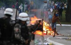 Tropas policiais se protegem com escudos enquanto manifestantes jogam pedras durante um protesto antes do jogo Uruguai x Nigéria pela Copa das Confederações, na Fonte Nova, em Salvador 20/6/2013. REUTERS/Kai Pfaffenbach