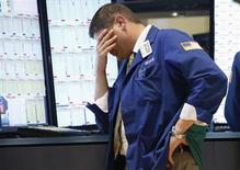 Трейдер на Нью-Йоркской фондовой бирже 20 июня 2013 года. Американские фондовые рынки снизились более чем на 2 процента в четверг, так как ФРС сообщила о намерении сократить объем скупки облигаций в этом году. REUTERS/Brendan McDermid