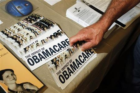 A Tea Party member reaches for a pamphlet titled ''The Impact of Obamacare'', at a ''Food for Free Minds Tea Party Rally'' in Littleton, New Hampshire October 27, 2012. REUTERS/Jessica Rinaldi