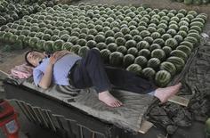 Торговец арбузами спит на рынке в Чанчжи в китайской провинции Шаньси 28 мая 2012 года. Растущее число китайских банкиров считает, что во втором квартале 2013 года ситуация в экономике незначительно ухудшилась по сравнению с первым, свидетельствуют результаты опроса, проведенного центробанком. REUTERS/Stringer