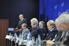 """Russian President Vladimir Putin (back) delivers a speech during a meeting entitled as """"Energy Club Summit: Reshaping Global Oil Markets"""" at the St. Petersburg International Economic Forum in St. Petersburg, June 21, 2013. Russian state-controlled oil company Rosneft will secure around $70 billion from China in upfront payments for crude deliveries, Russian President Vladimir Putin said on Friday. REUTERS/Mikhail Klimentyev/RIA Novosti/Kremlin"""