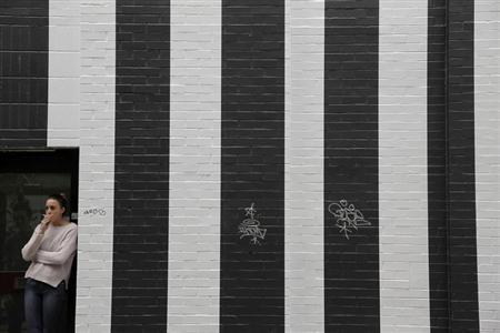 A woman smokes a cigarette in a doorway in London April 22, 2013. REUTERS/Stefan Wermuth