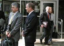Former Enron Chief Executive Jeffrey Skilling (2L) and attorney Daniel Petrocelli (L) talk to reporters as former Enron Chairman and CEO Kenneth Lay (R) and his wife Linda leave Federal court in Houston April 19, 2006. REUTERS/Richard Carson