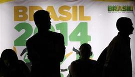 """Silhuetas de pessoas são vistas diante de propaganda da Copa do Mundo de 2014 no Brasil enquanto esperam ônibus, em Recife. A Fifa recebeu bem o pronunciamento à nação feito pela presidente Dilma Rousseff, em que ela pediu à população que conceda a """"mesma acolhida generosa"""" que o Brasil recebeu em outras Copas do Mundo, e reafirmou, neste sábado, a colaboração entre a entidade máxima do futebol e o governo para a realização da Copa das Confederações e do Mundial do ano que vem. 21/06/2013 REUTERS/Marcos Brindicci"""