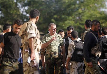 Colonel Abdul-Jabbar al-Aqidi, commander of the rebels' Military Council in Aleppo, is seen among members of Ghurabaa al-Sham brigade in the Al-Sakhour neighborhood of Aleppo, June 21, 2013. REUTERS/Muzaffar Salman