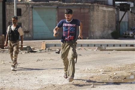 A Free Syrian Army fighter drops his gun as he runs for cover at the frontline in the Al-Sakhour neighborhood of Aleppo, June 21, 2013. REUTERS/Muzaffar Salman