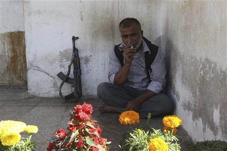 A Free Syrian Army fighter smokes a cigarette during his break near the frontline in the Al-Sakhour neighborhood of Aleppo, June 21, 2013. REUTERS/Muzaffar Salman