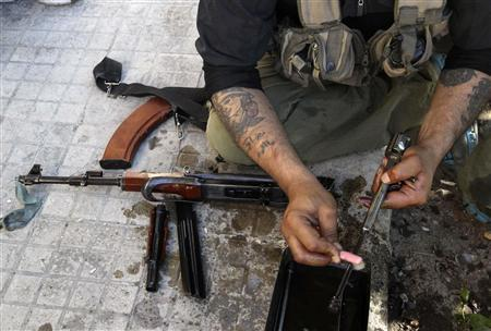 A Free Syrian Army fighter cleans his weapons at the frontline in the Al-Sakhour neighborhood of Aleppo, June 21, 2013. The tattoo reads ''I want your blessings, Mother'. REUTERS/Muzaffar Salman
