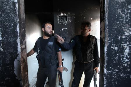 Members of Sheikh Ali Khatib battalion talk to each other inside a burnt house near Hanano Barracks, which is controlled by forces loyal to Syria's President Bashar al-Assad, in Aleppo, June 21, 2013. REUTERS/Nour Kelze