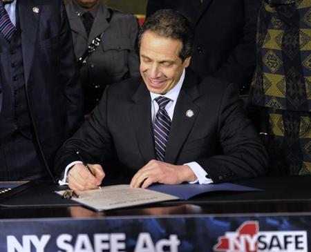 New York Governor Andrew Cuomo signs the New York Secure Ammunition and Firearms Enforcement Act at the Capitol in Albany, New York January 15, 2013. REUTERS/Hans Pennink