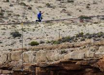 Daredevil Nik Wallenda gives a thumbs-up sign as he nears the end, after walking on a two-inch (5-cm) diameter steel cable rigged 1,400 feet (426.7 metres) across more than a quarter-mile deep remote section of the Grand Canyon near Little Colorado River, Arizona June 23, 2013. REUTERS/Mike Blake