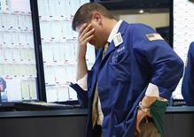 Трейдер на Нью-Йоркской фондовой бирже 20 июня 2013 года. Американские фондовые рынки выросли в пятницу, но снизились за неделю из-за планов ФРС сократить объем скупки облигаций в этом году. REUTERS/Brendan McDermid