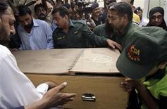 Медицинские работники и спасатели переносят коробку с телом погибшего иностранного туриста из кареты скорой помощи в морг в Исламабаде 23 июня 2013 года. Ночное нападение на международный лагерь альпинистов в горах северного Пакистана унесло жизни по меньшей мере 11 человек, включая трех украинцев, отдыхавших перед восхождением на одну из самых высоких и сложных вершин мира, что стало самой дерзкой и кровавой атакой на туристов в знаменитых горах. REUTERS/Sohail Shahzad