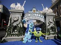 """Персонажи """"Университета монстров"""" позируют перед премьерой фильма в Голливуде, 17 июня 2013 года. """"Университет монстров"""", приквел анимационного блокбастера 2001 года """"Корпорация монстров"""", собрал в свой дебютный уикенд $82 миллиона и стал лидером проката Северной Америки. REUTERS/Mario Anzuoni"""