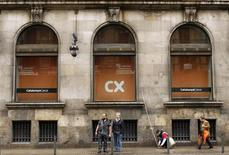 People are seen in front of the Catalunya Caixa bank at its headquarters in Barcelona, March 6, 2013. REUTERS/Albert Gea