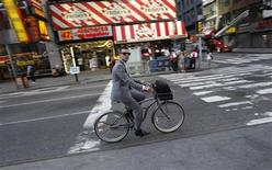 A man rides a bicycle down 7th Avenue through Times Square in the early morning in this June 21, 2010 file photo. REUTERS/Mike Segar/Files