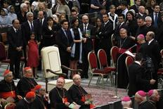 An empty papal throne is pictured as Archbishop Rino Fisichella (R) reads a message from Pope Francis before a RAI National Symphony Orchestra concert, directed by conductor Juraj Valcuha of Slovakia, in Paul VI hall at the Vatican June 22, 2013. REUTERS/Giampiero Sposito