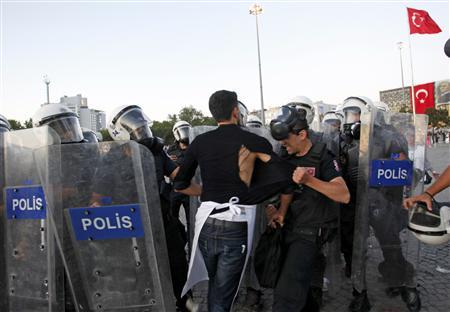 A riot policeman tear the shirt of a protester at Taksim Square in Istanbul June 22, 2013. REUTERS/Murad Sezer