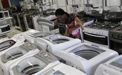 Mulher com filha examina uma máquina de lavar em loja das Casas Bahia, em São Paulo. O setor varejista projeta uma alta de 6,4 por cento para o faturamento do setor em junho na comparação com o mesmo período do ano passado, segundo o Instituto para Desenvolvimento do Varejo (IDV), ressaltando que a alta do dólar e as manifestações realizadas pelo Brasil podem impactar nesse avanço. 18/02/2013. REUTERS/ Nacho Doce
