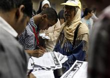 """People sign their names as volunteers from the opposition """"Rebel!"""" campaign stop passengers in the underground to collect signatures for their campaign ahead of a planned anti-Mursi protest at the end of the month, in Cairo June 25, 2013. REUTERS/Asmaa Waguih"""
