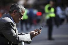 A man uses a smartphone to perform various tasks in New York September 25, 2009. REUTERS/Natalie Behring