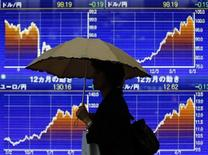 Женщина с зонтом проходит мимо брокерской конторы в Токио 11 июня 2013 года. Доллар дешевеет к иене на фоне опасений за Китай, но получает поддержку со стороны макроэкономической статистики США и роста доходности американских облигаций. REUTERS/Yuya Shino