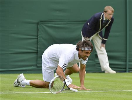 Marcos Baghdatis of Cyprus slips during his men's singles tennis match against Marin Cilic of Croatia at the Wimbledon Tennis Championships, in London June 24, 2013. REUTERS/Toby Melville