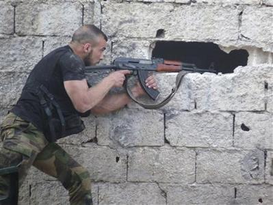 A Free Syrian Army fighter aims his weapon as he takes a defensive position in Qaboun area in Damascus June 20, 2013. REUTERS-Yaman Alrandi