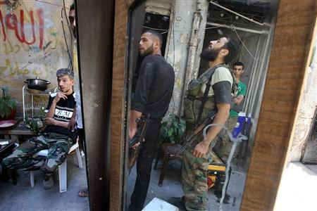 Free Syrian Army fighters carrying their weapons are reflected in a mirror in the old city of Aleppo June 24, 2013. REUTERS-Muzaffar Salman