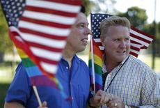 Married couple Bill Hacket, 53, (L) and Thom Uber wave flags in West Hollywood, California after the United States Supreme court ruled on California's Proposition 8 and the federal Defense of Marriage Act, June 26, 2013. REUTERS/Lucy Nicholson