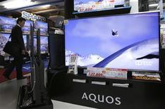Homem olha televisores Aquos da fabricante japonesa Sharp em loja de eletrônicos, em Tóquio. A japonesa Sharp, uma das principais fornecedoras de telas para a Apple, anunciou nesta quinta-feira que formará uma aliança de 2,9 bilhões de dólares com a estatal China Electronics. 14/05/2013 REUTERS/Toru Hanai