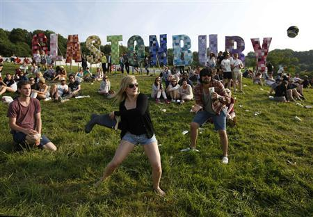 Festival goers play baseball, batting a beer can with a wellington boot, on the first day of Glastonbury music festival at Worthy Farm in Somerset, June 27, 2013. REUTERS/Olivia Harris
