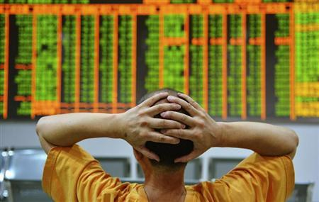 An investor sits in front of an electronic board showing stock information at a brokerage house in Hangzhou, Zhejiang province, June 24, 2013. REUTERS/China Daily