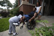 Miles Turner is helped up the stairs to his home by his mother Angela and his father Miles in Chicago, Illinois, June 9, 2013. REUTERS/Jim Young (UNITED STATES - Tags: CIVIL UNREST CRIME LAW)