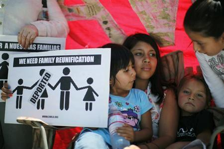 Jirasol Hernandez (L-R), 4, Naelli Martinez, 11, and Sasha Carmen, 4, try to stay out of the heat at a 24-hour vigil calling on Congress to pass immigration reform in Los Angeles, June 27, 2013. REUTERS-Lucy Nicholson