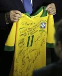 O presidente da Fifa, Joseph Blatter, segura camisa do Brasil autografada que será dada ao ex-presidente sul-africano Nelson Mandela. REUTERS/Paulo Whitaker