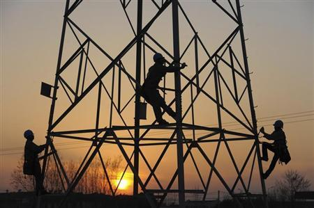 Employees check on an electricity pylon in Chuzhou, Anhui province, May 1, 2013. REUTERS/China Daily
