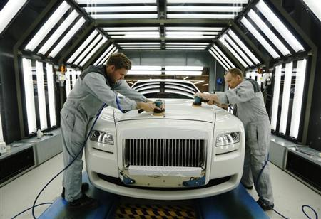 Employees Joe Don (L) and Darren Lowarson give a Rolls Royce Ghost its final finish polish at the Rolls Royce Motor Cars factory at Goodwood near Chichester in southern England April 24, 2013. B Photograph taken on April 24, 2013. REUTERS/Luke MacGregor