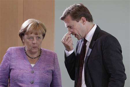 German Chancellor Angela Merkel chats with German government spokesman Steffen Seibert (R) before the weekly cabinet meeting in Berlin, September 19, 2012. REUTERS/Tobias Schwarz