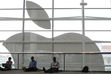 Attendees sit in front of an Apple logo at the Apple Worldwide Developers Conference (WWDC) 2013 in San Francisco, California June 10, 2013. REUTERS/Stephen Lam