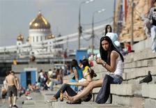 Люди сидят на набережной Москвы-реки 22 мая 2011 года. Знойная погода сохранится в Москве на текущей рабочей неделе, ожидают синоптики. REUTERS/Denis Sinyakov