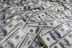 Стодолларовые купюры в банке в Сеуле 9 января 2013 года. Доллар отступил о четырехнедельного максимума к корзине валют во вторник, так как аппетит к риску улучшился благодаря сильным производственным данным из крупных мировых экономик, перевесив опасения об отмене стимулов в США. REUTERS/Lee Jae-Won