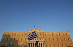 Женщина поднимает флаг Греции над площадью Синтагма во время акции протеста в Афинах 30 июня 2011 года. У Греции есть три дня, чтобы убедить своих кредиторов, что она может выполнить условия, сопровождающие ее международную программу помощи, и получить следующий финансовый транш, сообщили во вторник четыре представителя еврозоны. REUTERS/John Kolesidis