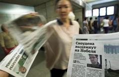 """Fotografia de Edward Snowden, ex-prestador de serviço de uma agência espiã dos EUA, é vista estambpada em um jornal distribuído no metrô de Moscou. Snowden retirou seu pedido de asilo político à Rússia depois que o presidente russo, Vladimir Putin, disse que ele deveria parar de """"prejudicar os nossos parceiros americanos"""", afirmou o Kremlin nesta terça-feira. 2/07/2013. REUTERS/Maxim Shemetov"""