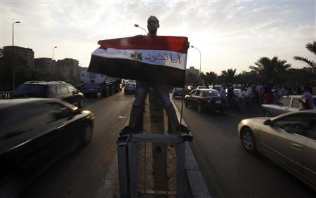 A protester opposing Egyptian President Mohamed Mursi holds an Egyptian flag as he shouts slogans against Mursi and members of the Muslim Brotherhood in front of the Presidential Palace ''Qasr Al Quba'' in Cairo July 2, 2013. REUTERS/Amr Abdallah Dalsh