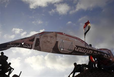 Supporters of President Mohamed Mursi carry a banner with his pictures during a protest to counter anti-Mursi protests elsewhere in Alexandria, July 2, 2013. REUTERS/Asmaa Waguih