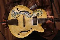"Luis Martin, Spanish guitarist from the band ""Lobos Negros"", shows a ceramic guitar in Madrid July 3, 2013. REUTERS/Juan Medina"