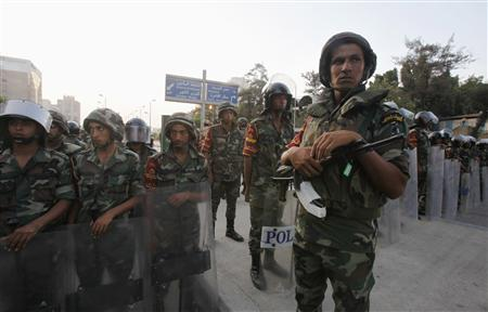 Army soldiers stand guard in front of protesters who are against Egyptian President Mohamed Mursi, near the presidential palace in Cairo July 3, 2013. The Egyptian president's national security adviser said on Wednesday that a ''military coup'' was under way and army and police violence was expected to remove pro-Mursi demonstrators. REUTERS/Amr Abdallah Dalsh