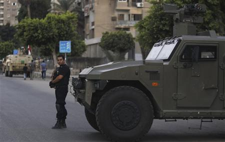 A police special forces member is seen near army soldiers taking positions in front of protesters who are against Egyptian President Mohamed Mursi, near the Republican Guard headquarters in Cairo July 3, 2013. REUTERS/Amr Abdallah Dalsh